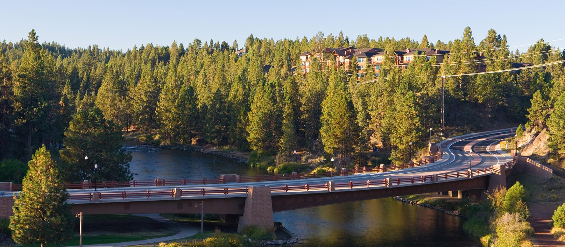 Reed Market Bridge in Bend Oregon crossing the Deschutes River with ponderosa pine trees in the background.