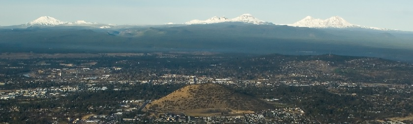 Photo of Bend with Pilot Butte in foreground and mountains in the background.