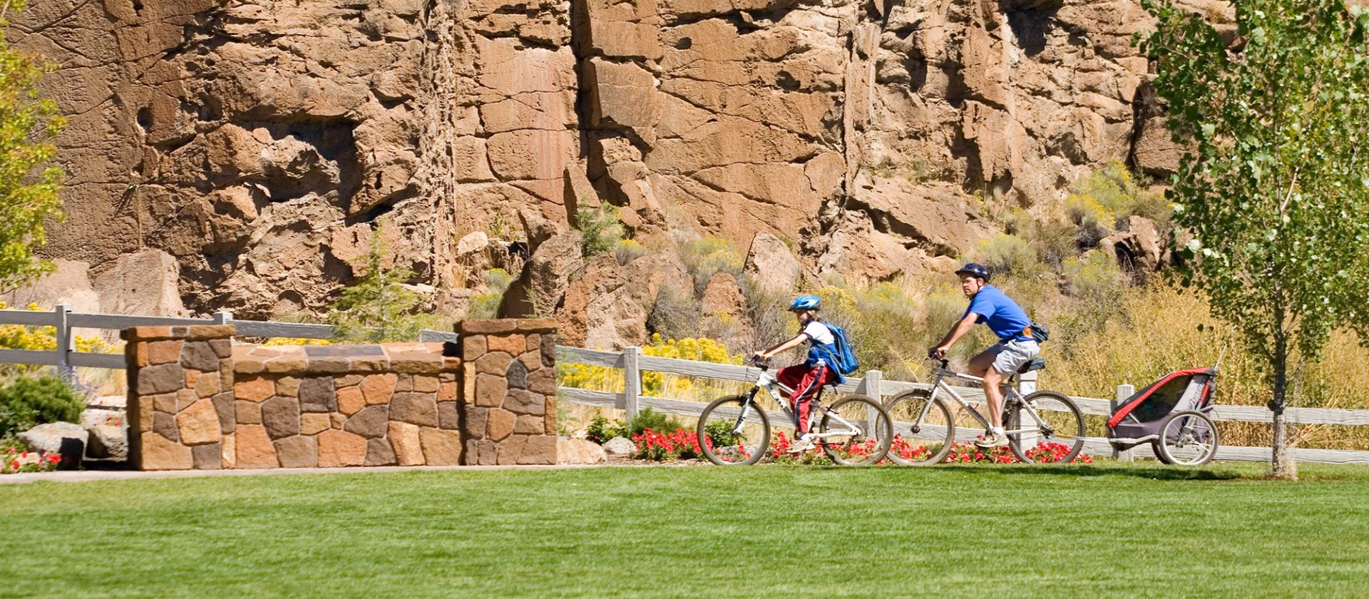 Family biking through park with a rocky cliff in the background.