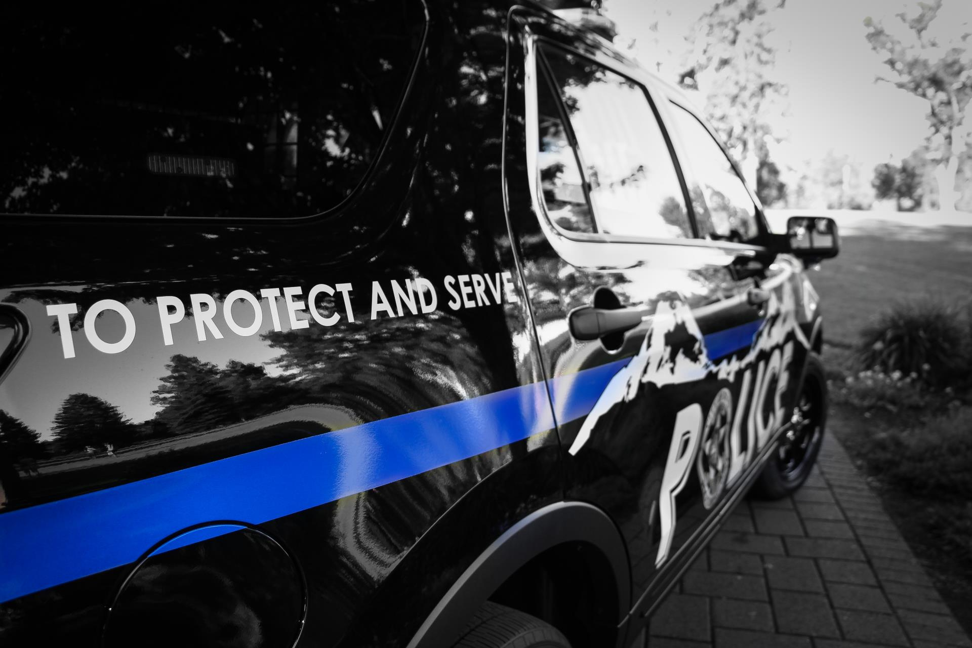Close-up photo of a Police SUV highlighting the words To Protect and Serve