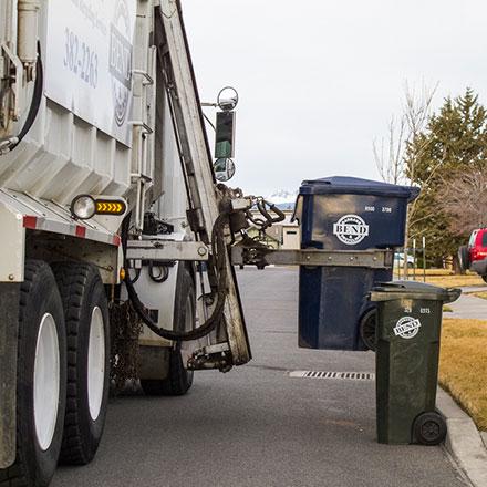 Bend garbage truck picking up trash can