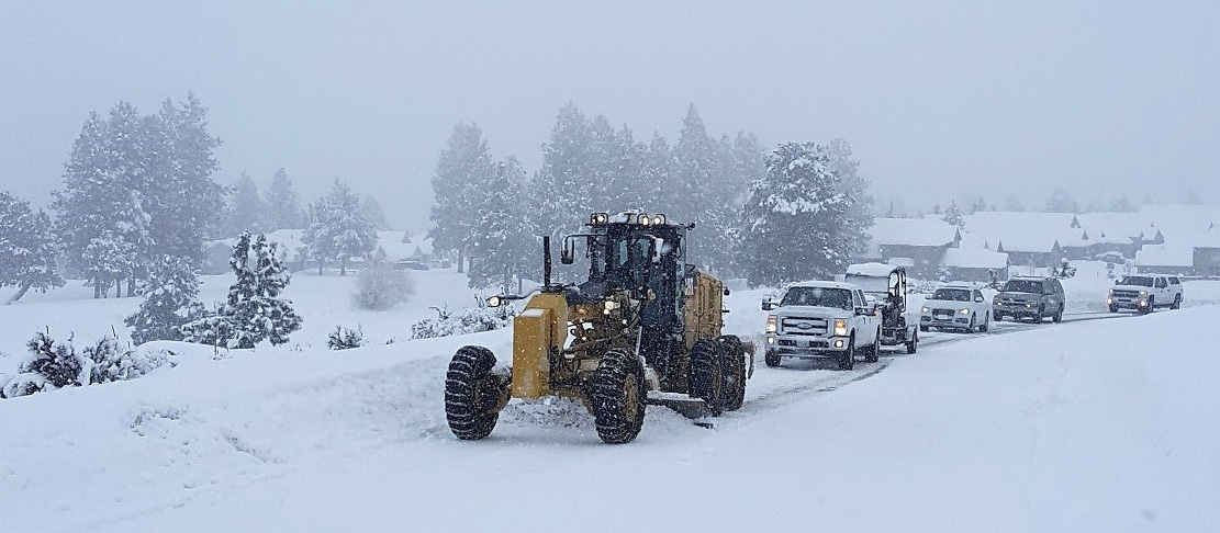 Grader plowing snow off of the road during snowstorm with line of cars behind.