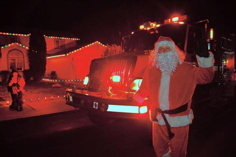 City of Bend Santa Express. Santa Claus standing in front of City Fire truck.