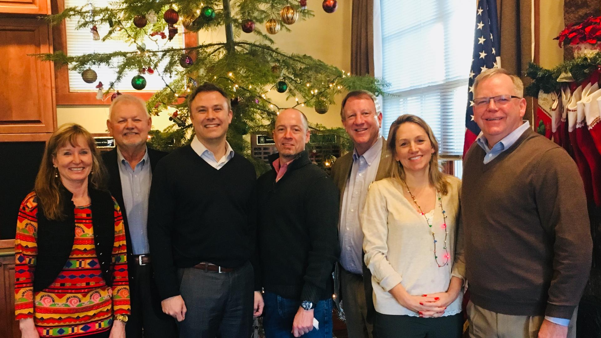 Eric King and the executive team standing in front of a Christmas tree. Merry Christmas!