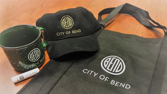 City of Bend swag including a ceramic mug, chapstick, baseball cap and shopping bag.