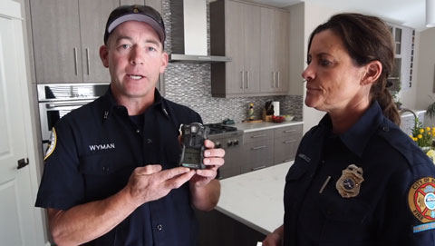 Two EMS staff demonstrating how to use a carbon monoxide detector.