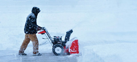 Man clearing sidewalk with a snowblower.
