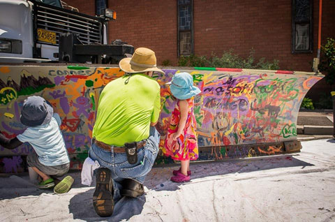Father and kids painting on snowplow blade.
