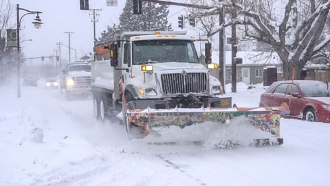 Snowplow plowing Bend street.