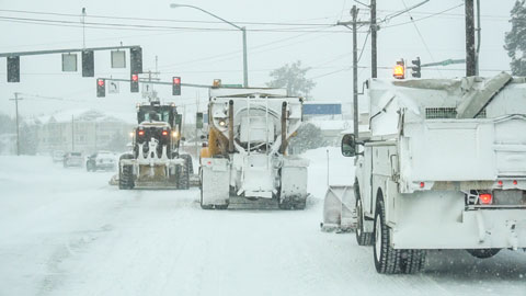 Three snowplows plowing during a snowstorm.