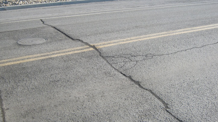 Photo of a road with a large crack in the pavement.