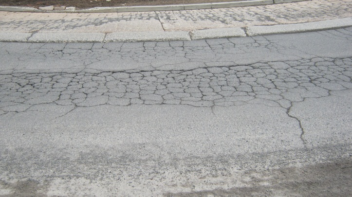 Photo of a deteriorated road with many cracks.