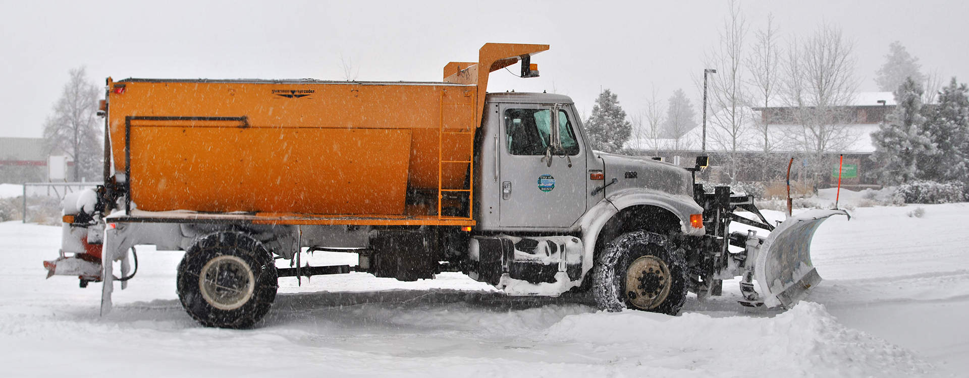 City of Bend snowplow parked as it snows all around.