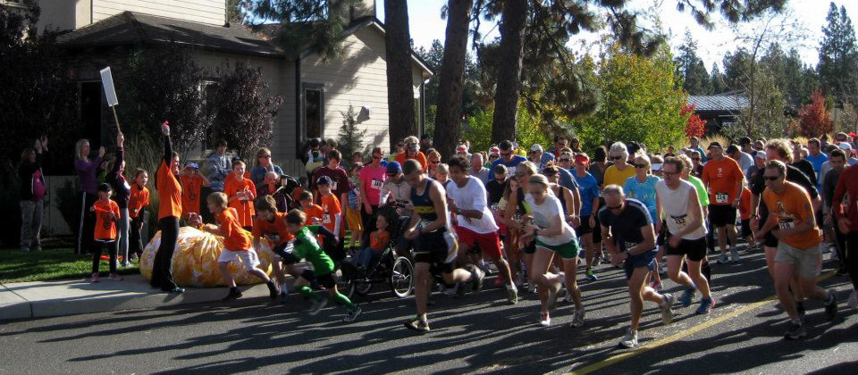 Large group of people leaving the starting line of a race through town.