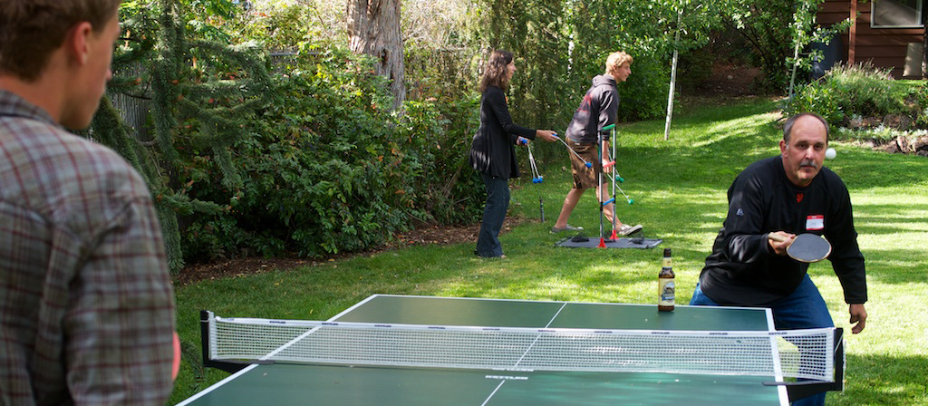 Man and boy playing ping pong outdoors on a sunny day.