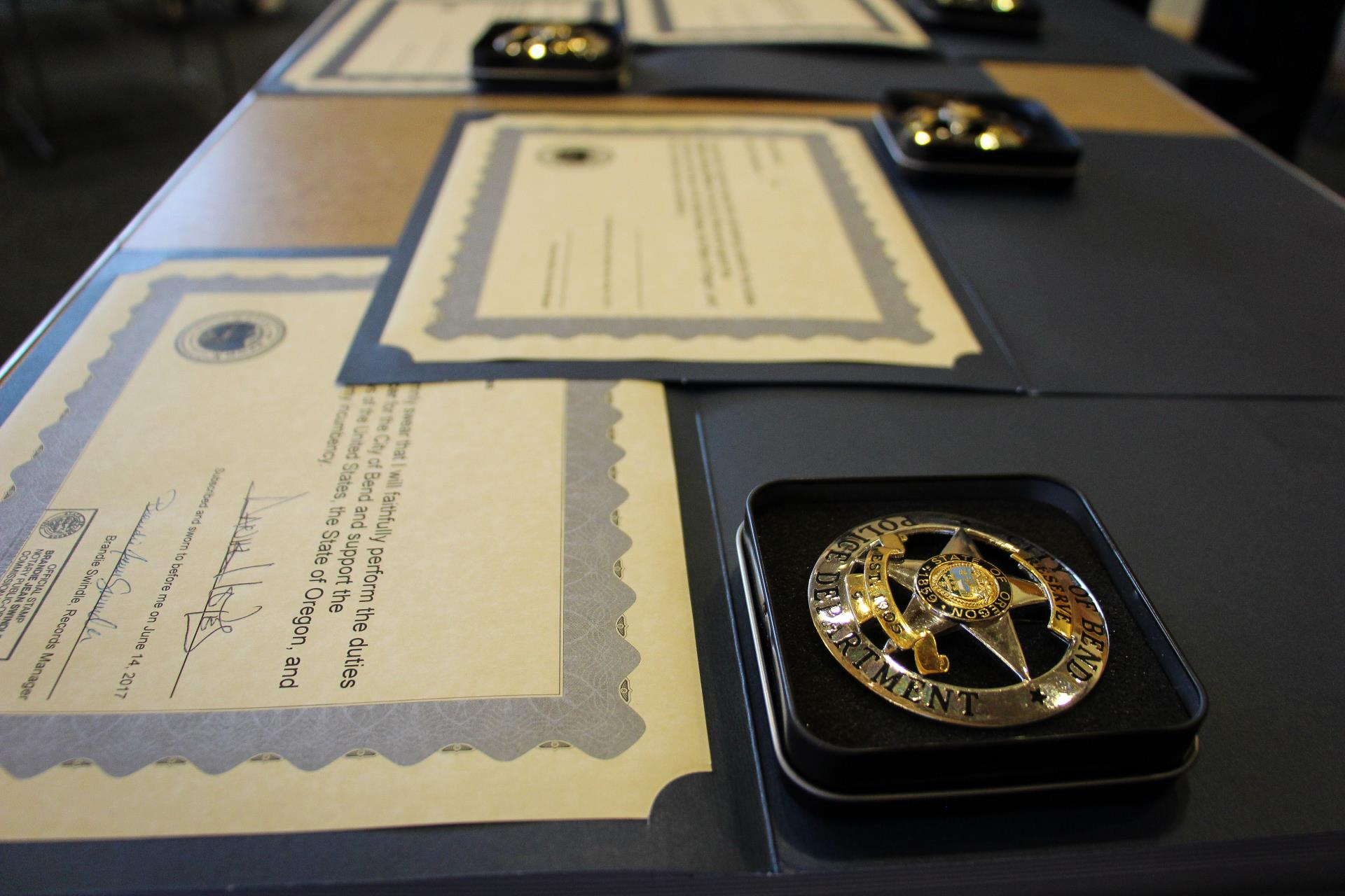 badge and certificates laid out on a table