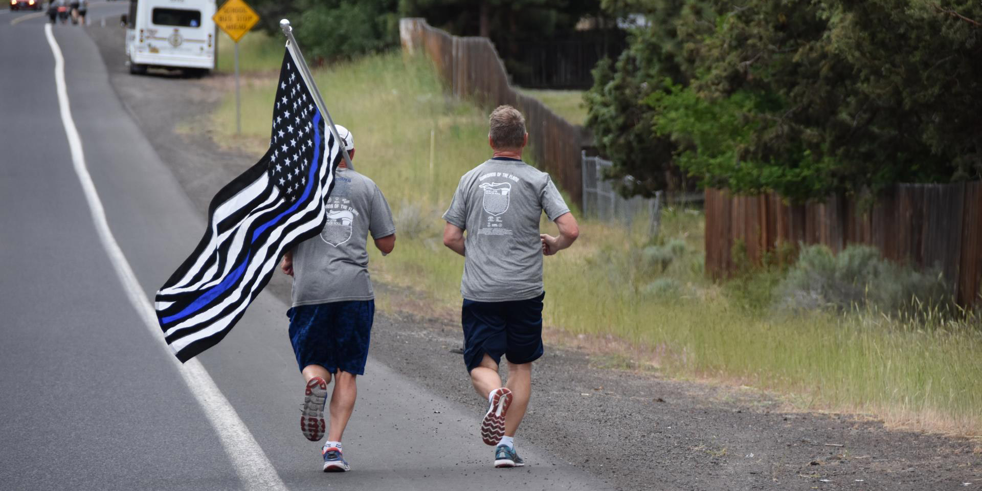 Officers running along road carrying Police Thin Blue Line flag