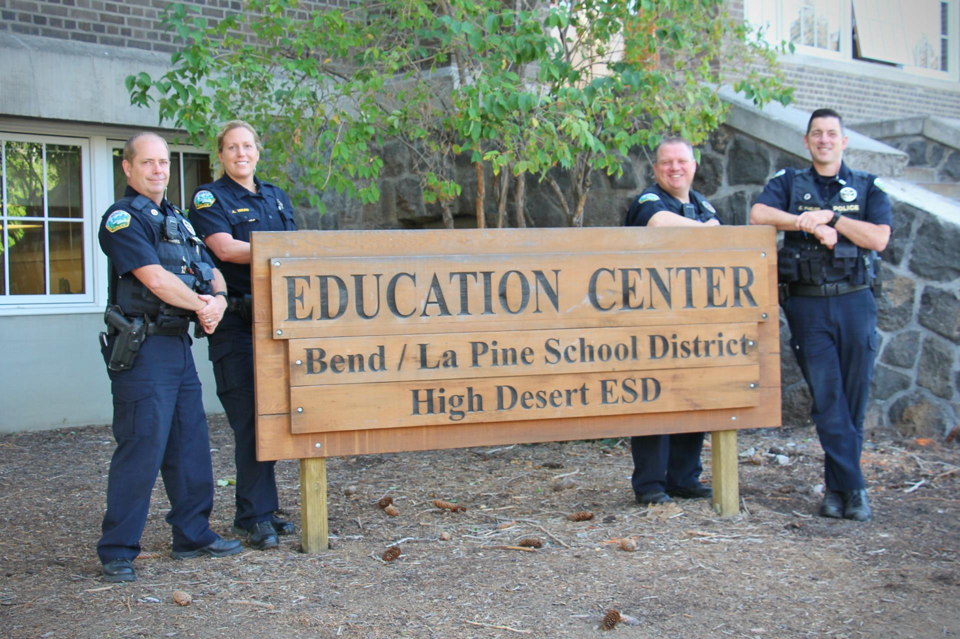 four school resource officers in front of a education center sign