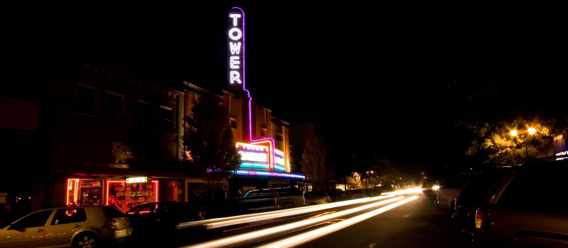 Tower Theater at night with vehicle light trails in the foreground