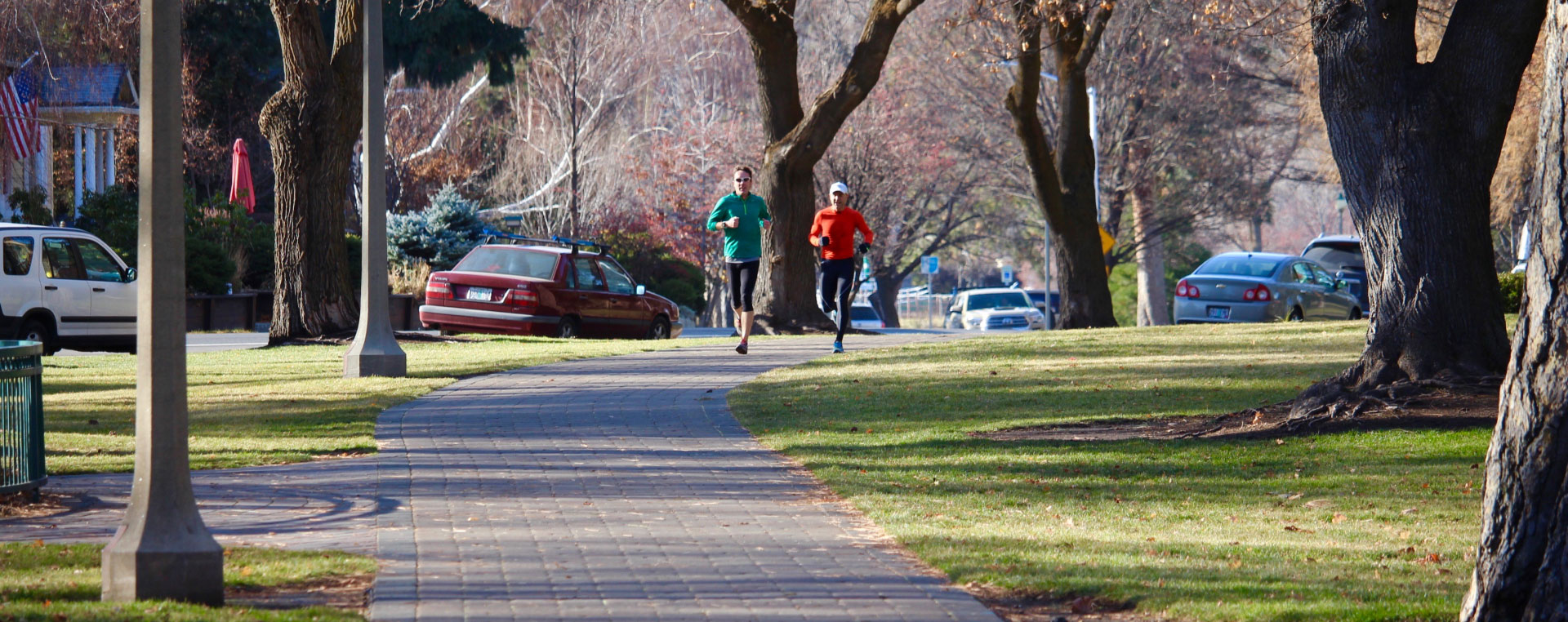 Image of cars parked along Riverside Boulevard with runners running in Drake Park