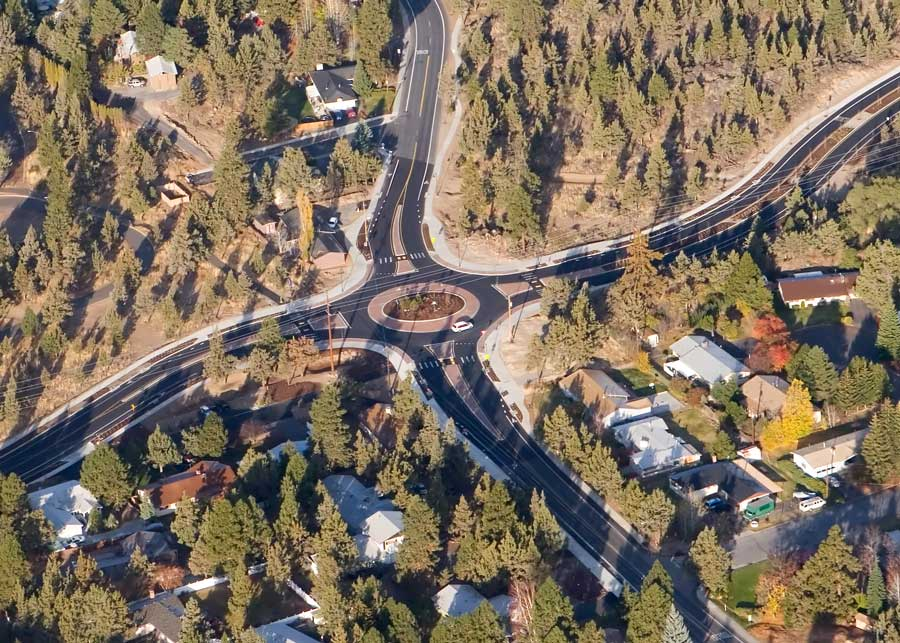 Arial view of  roundabout surrounded by trees and homes.