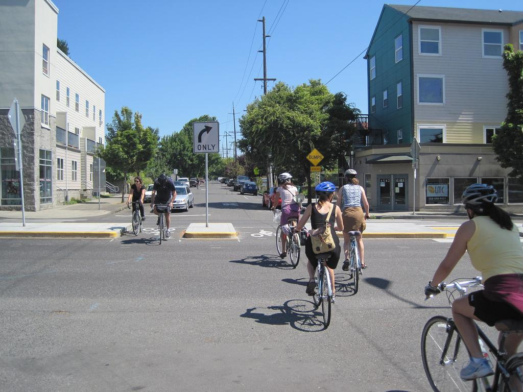 Bicyclists crossing a two-lane street through a traffic diverter near a city neighborhood.