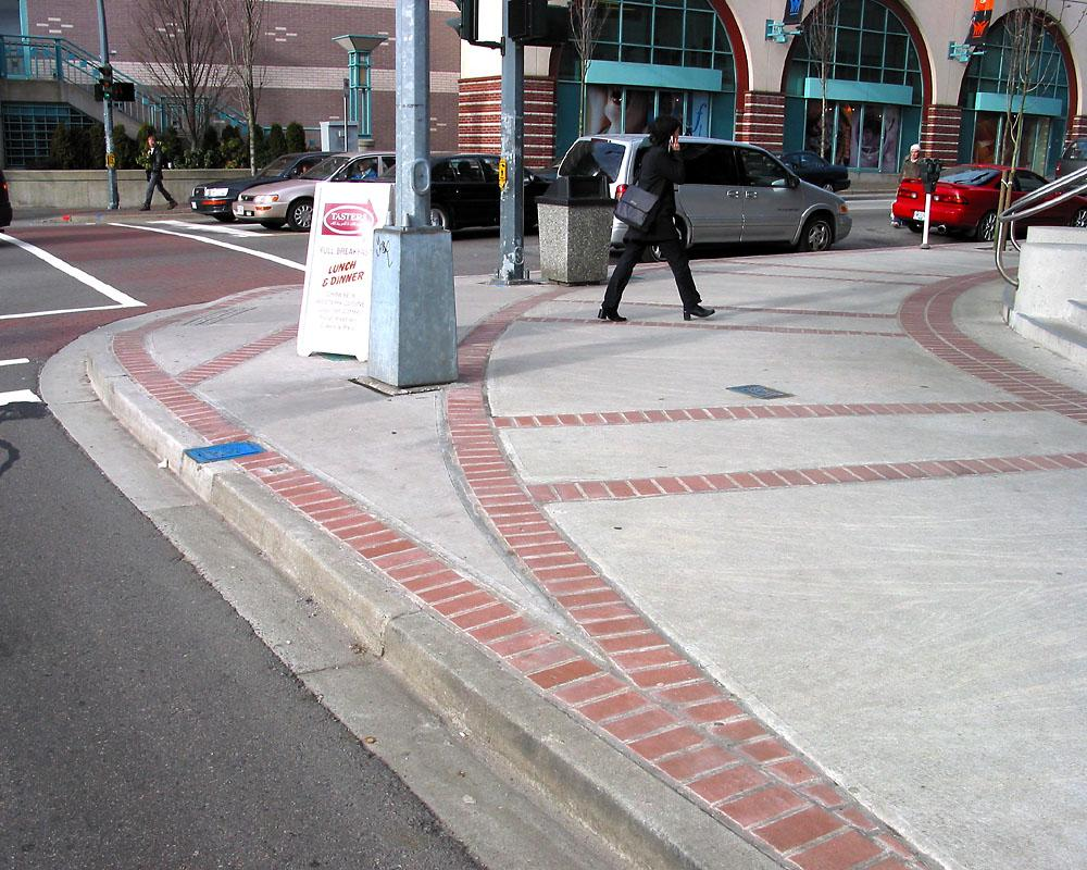 A large, curved sidewalk corner at a crosswalk on an urban street. Signal and crosswalk posts are set back a good distance from the street.