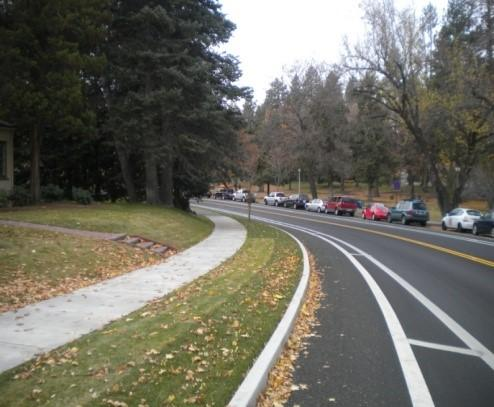 A buffered bike lane between a curb and a two lane road.