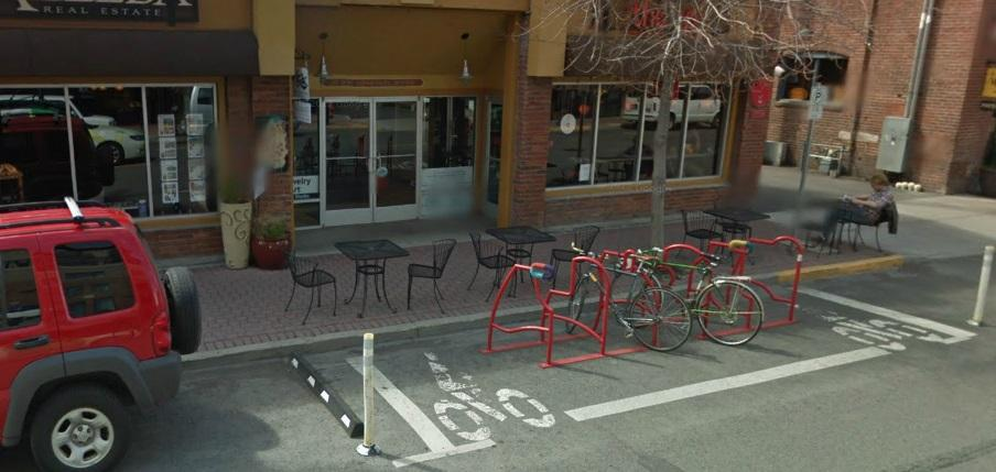 Image of a bike corral in the street in front of a downtown business.  The corral has safety markers on either corner, and a bumper strip between it and an adjacent parking spot.