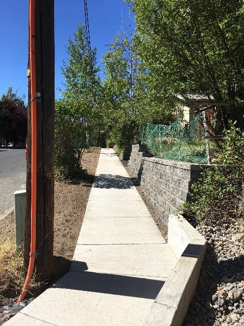 Shaprd Rd 3 After Photo - reconstructed sidewalk continuing along street, new retaining wall and trimmed vegetation
