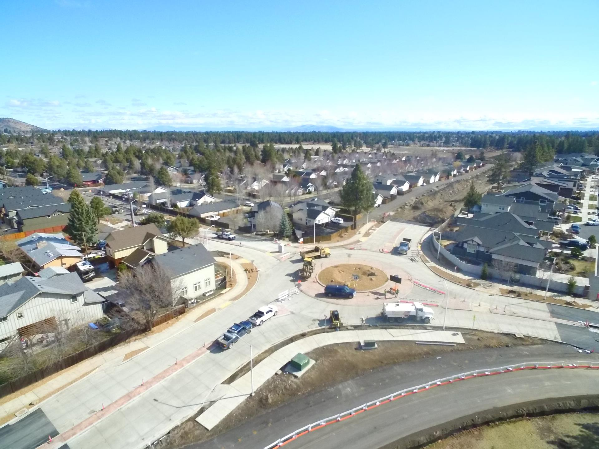 An Aerial photo overlooking work crews and equipment at the Murphy/Brosterhous roundabout, with surrounding residintial neighborhood and pine trees and Pilot Butte in the background.