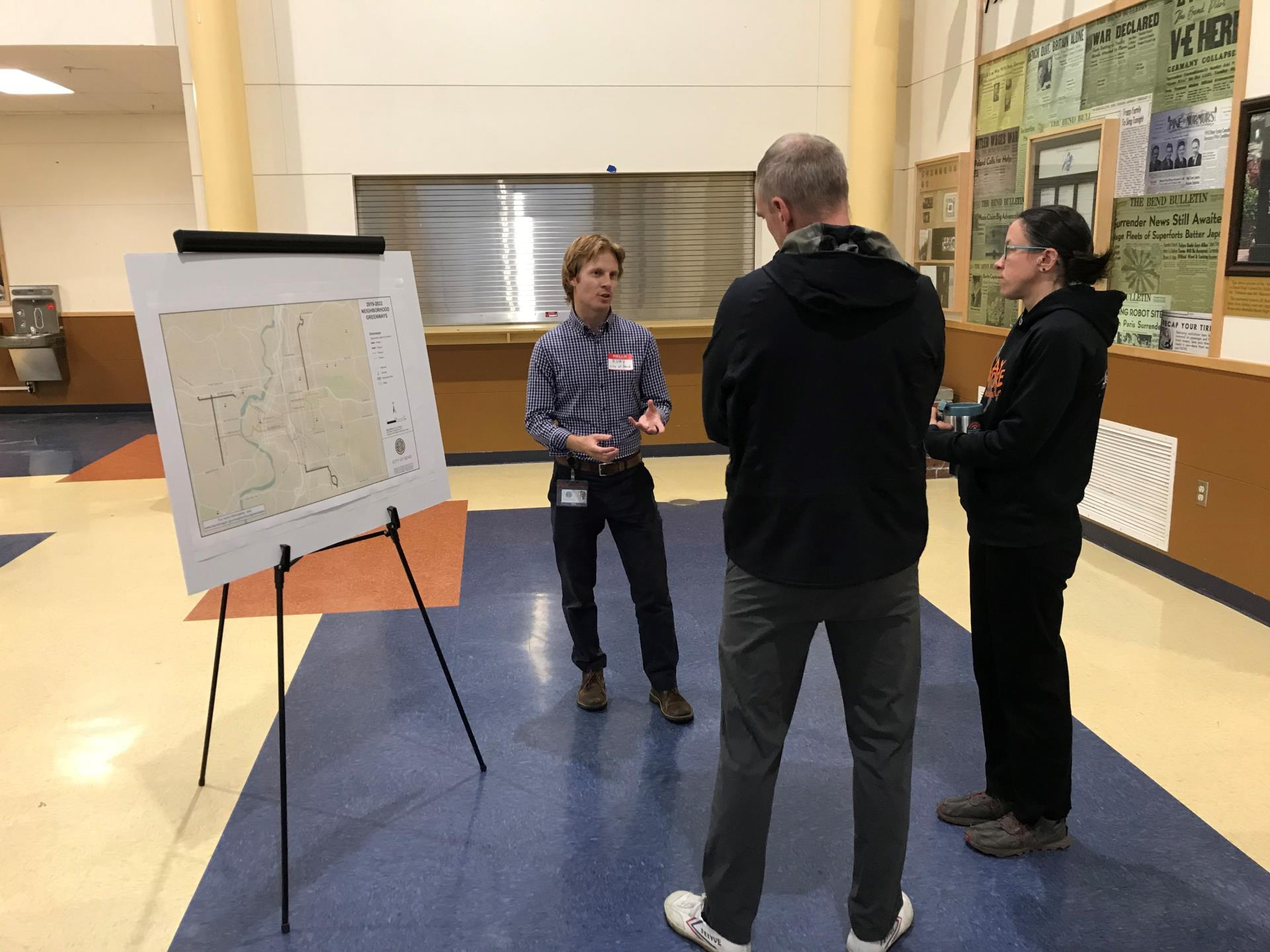 Photo of City project manager speaking with community members next to project map at open house