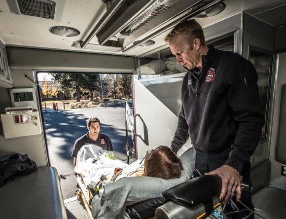 City of Bend Emergency Medical Services loading a woman into ambulance.