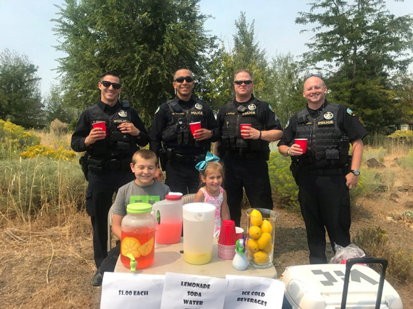 City of Bend Police officers drinking lemonade in front of kids' lemonade stand.