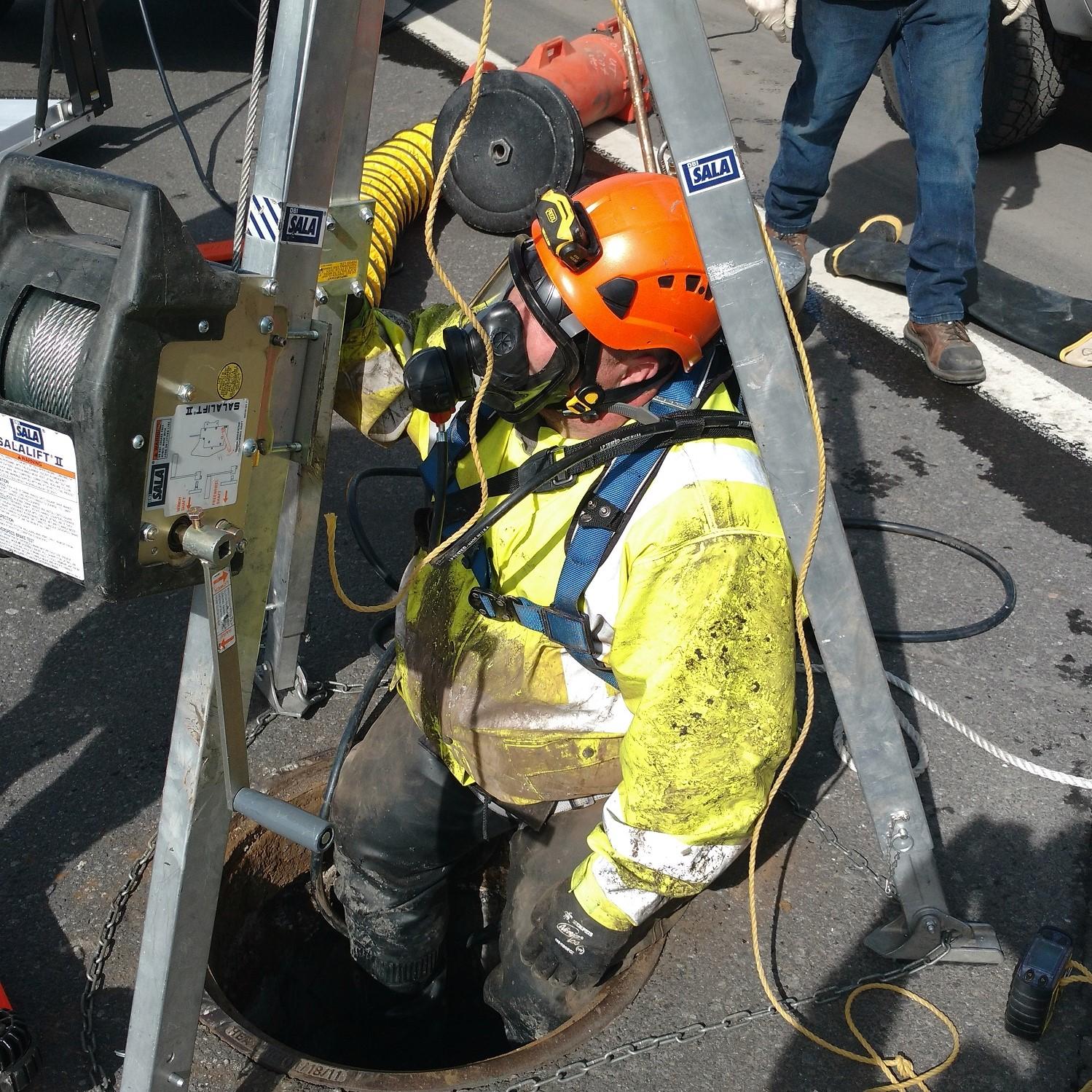 Utility crew entering manhole.