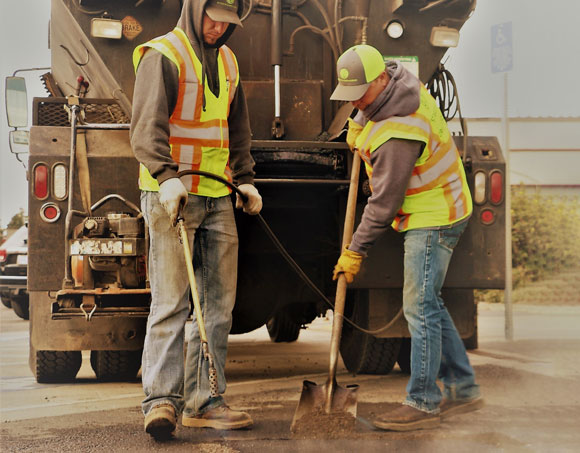 Two Streets Department crew members fixing a pothole.