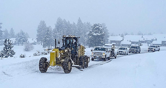 Cars trailing a grader plowing snow.