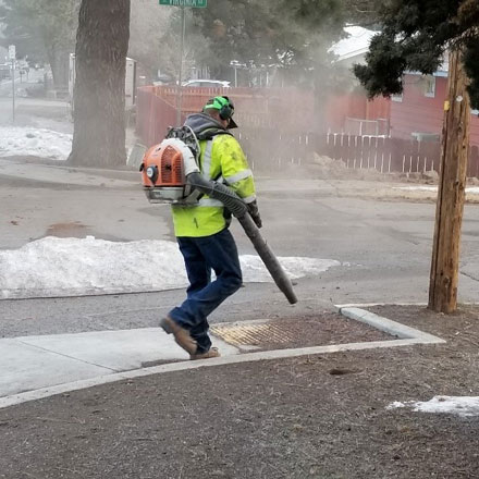 Streets department worker cleaning accumulated dirt from curb ramp.