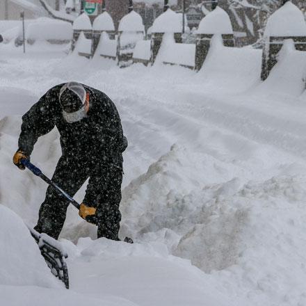 Man shoveling snow after record snowfall.