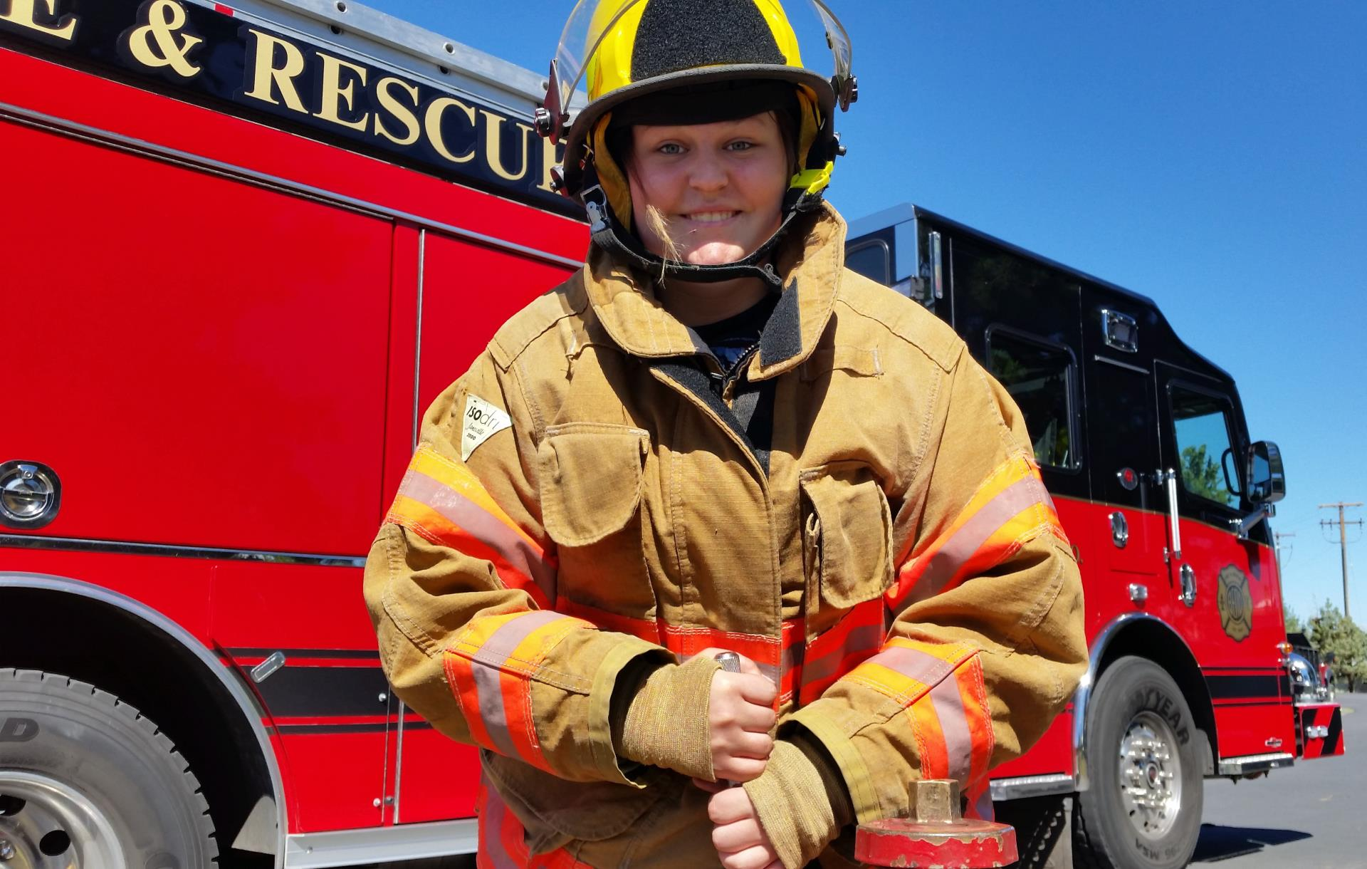 Camp Fire Axe Student standing in front of Fire Engine